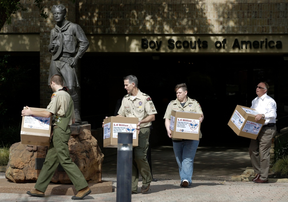 From left, Eagle Scout Will Oliver, former Scoutmaster Greg Bourke, former den leader Jennifer Tyrrell and Eric Andresen, right, a parent of a gay scout, place boxes filled with a petition at the statue in front of the Boy Scouts of America headquarters in Dallas, Texas Monday, Feb. 4, 2013. (AP / Tony Gutierrez)