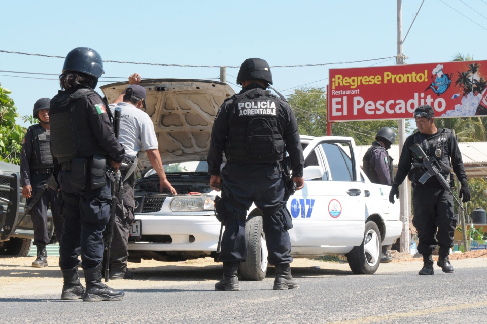 State police check a taxi at a roadblock due to stepped up security after masked armed men broke into a beach home, raping six Spanish tourists who had rented the house in Acapulco, Mexico, Tuesday, Feb. 5, 2013. (AP / Bernandino Hernandez)