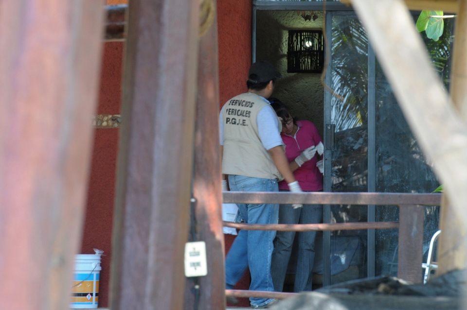 Police investigators work to obtain fingerprints on a door at the home where masked, armed men broke in, in Acapulco, Mexico, Tuesday Feb. 5, 2013. (AP / Bernandino Hernandez)