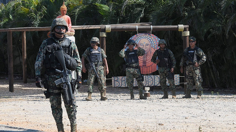 Mexican navy marines stand at a roadblock due to stepped up security after masked armed men broke into a beach home, raping six Spanish tourists who had rented the house in Acapulco, Mexico, Tuesday Feb. 5, 2013. (AP / Bernandino Hernandez)