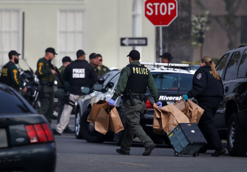 Police investigators carry evidence bags near the area where a shooting took place in Riverside, Calif, Thursday, Feb. 7, 2013. (AP / Jae C. Hong)