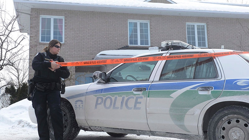 A police officer attaches police tape outside the house of Sen. Patrick Brazeau in Gatineau, Que., Thursday, Feb.7, 2013. (Adrian Wyld / THE CANADIAN PRESS)
