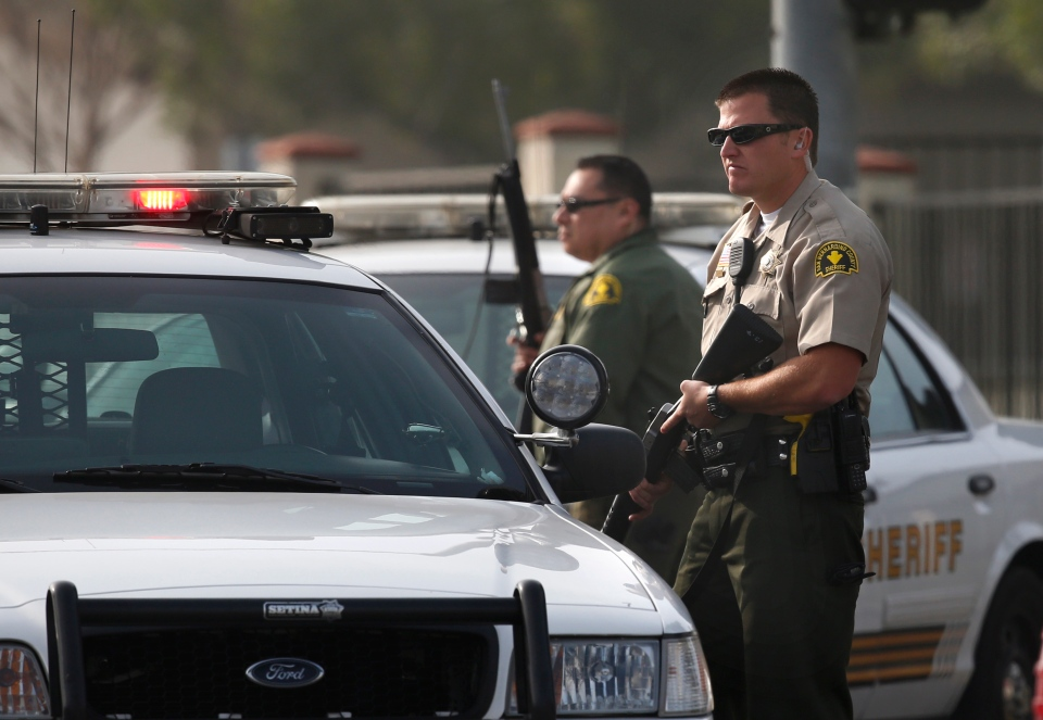 Two San Bernardino County sheriff's deputies stand guard near the area where a shooting took place in Riverside, Calif, Thursday, Feb. 7, 2013. (AP / Jae C. Hong)