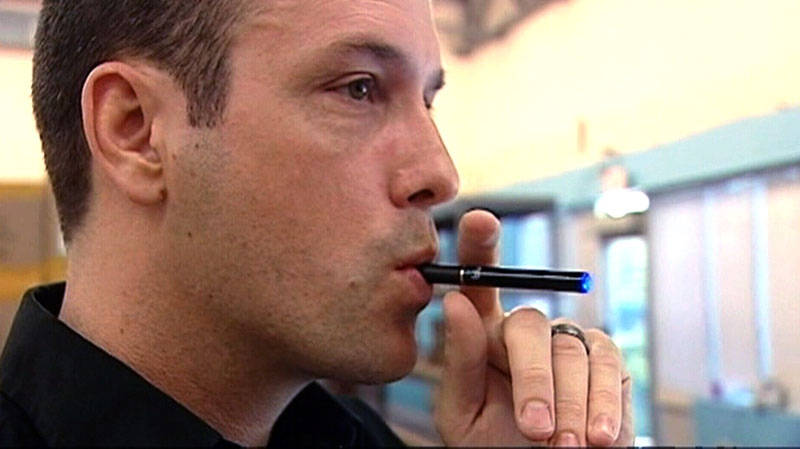 A man puffs on an e-cigarette in this undated image.