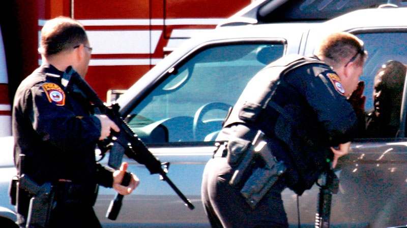 Police search the parking lot outside a Safeway where there has been a shooting involving Rep. Gabrielle Giffords, D-Ariz., in Tucson, Ariz. on Saturday, Jan. 8, 2011. (AP / Arizona Daily Star, Kelly Presnell)