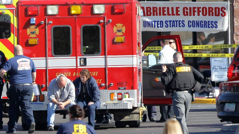 Emergency personnel work at the scene where Rep. Gabrielle Giffords, D-Ariz., and others were shot outside a Safeway grocery store in Tucson, Ariz. on Saturday, Jan. 8, 2011. (AP / Matt York)