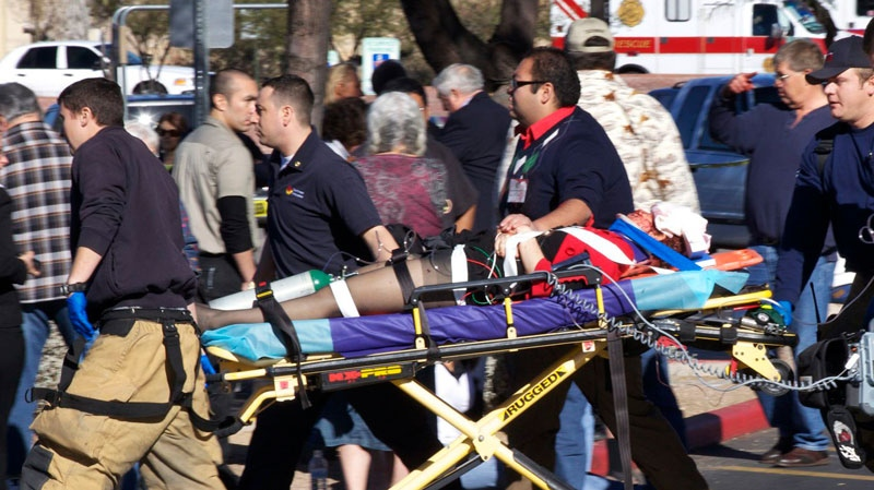 Emergency personnel use a stretcher to carry a shooting victim  outside a shopping center in Tucson, Ariz. on Saturday, Jan. 8, 2011. (AP / James Palka)