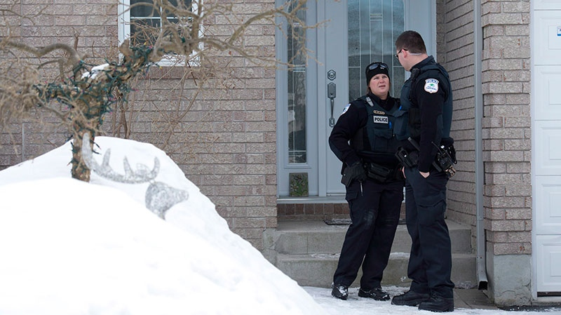 Gatineau police officers talk outside the house of Sen. Patrick Brazeau in Gatineau, Que., Thursday, Feb. 7, 2013. (Adrian Wyld / THE CANADIAN PRESS)