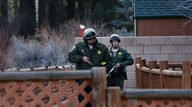 San Bernardino County sheriff's deputies search a home during a manhunt for former Los Angeles officer Christopher Dorner in Big Bear, Calif, Thursday, Feb. 7, 2013.  (AP / Jae C. Hong)