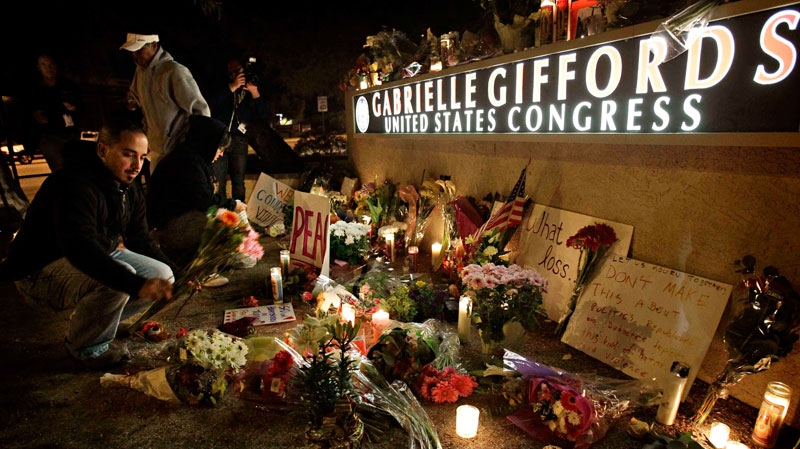 Mike Scionti, of Tucson, places flowers outside the offices of U.S. Rep. Gabrielle Giffords, D-Ariz., during a candlelight vigil for Giffords Saturday, Jan. 8, 2011 in Tucson, Ariz. (AP / Matt York)