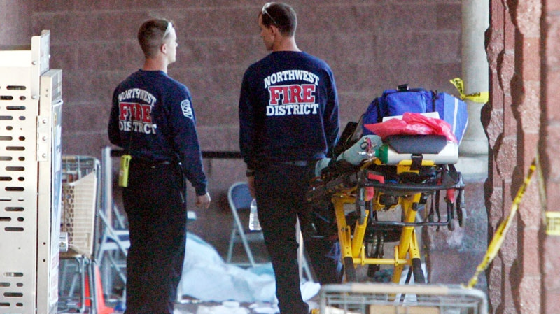 Emergency personnel stand at the scene of a shooting that authorities claim involved Rep. Gabrielle Giffords, D-Ariz., in Tucson, Ariz., on Saturday, Jan. 8, 2011. (AP / Arizona Daily Star, Dean Knuth)