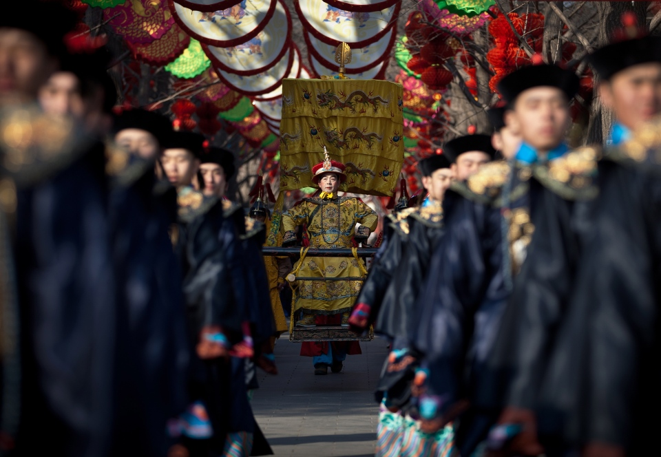 A Chinese actor dressed as Qing Dynasty emperor, center, sits on a sedan chair during a rehearsal of an ancient Qing Dynasty ceremony ahead of the upcoming Chinese New Year at Ditan Park in Beijing Friday, Feb. 8, 2013. (AP / Andy Wong)