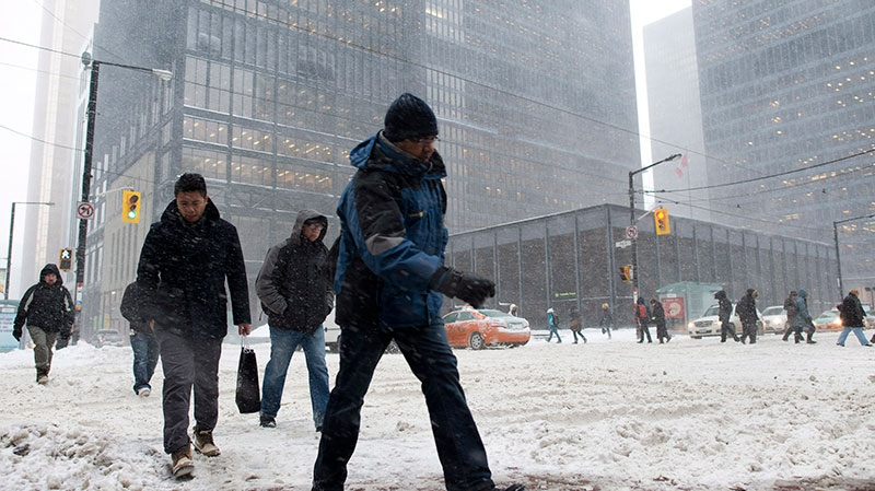 Pedestrians cross a snow-covered street in downtown Toronto on Friday, Feb. 8, 2013. (Graeme Roy / THE CANADIAN PRESS)