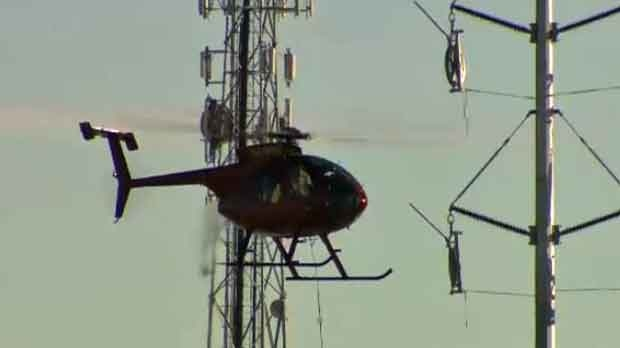 A chopper helps crews string cable for a new substation.