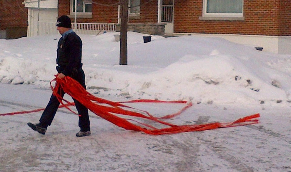 A police officer takes down police tape after a shooting incident in Dorval, Que., on Tuesday, Jan.22, 2013. A 12-year-old boy has been charged in connection with the shooting death of his older brother. (The Canadian Press/Peter Ray)