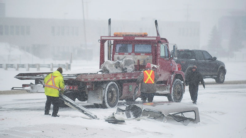 Workers clear parts of a vehicle following an accident on Highway 40 near Montreal, Friday, Feb. 8, 2013. (Graham Hughes / THE CANADIAN PRESS)