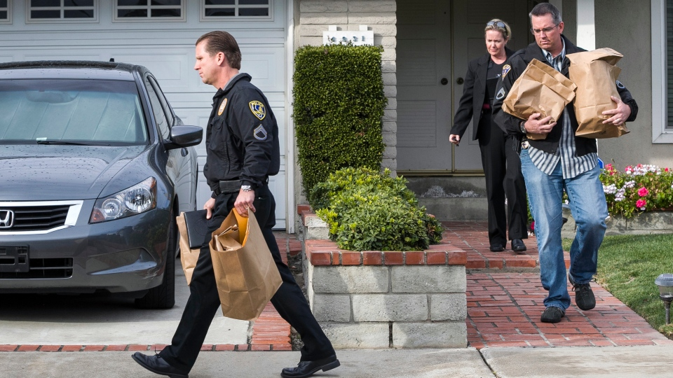 Police investigators take away evidence from the home of the mother of fugitive suspect former Los Angeles police officer Christopher Dorner, in La Palma, Calif., on Friday, Feb. 8, 2013. (AP Photo / Damian Dovarganes)