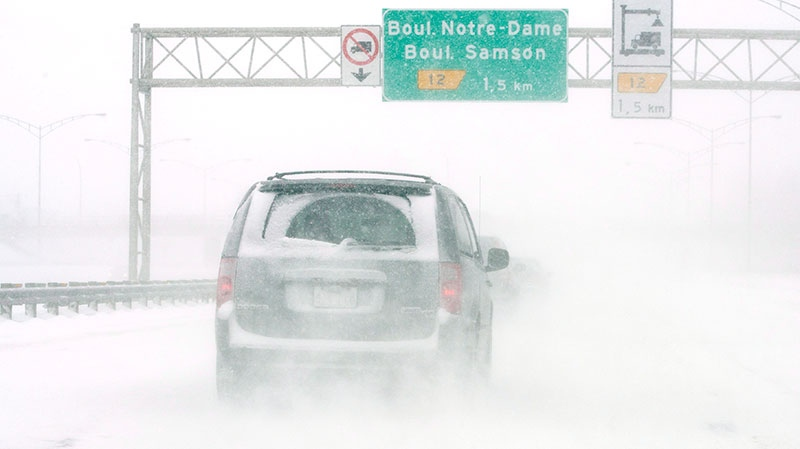 Motorists battle whiteout conditions on Highway 13 as a snowstorm dumps up to 15cm of snow in Laval, Que., Friday, Feb. 8, 2013. (Ryan Remiorz / THE CANADIAN PRESS)