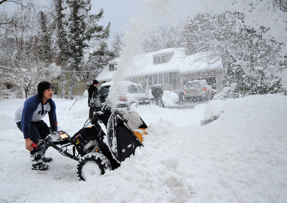 Eguin Belasquez steers a snow blower through mounds of snow as he helps his friend dig out of his driveway after a snow storm in Sea Cliff, N.Y. on Saturday, Feb. 9, 2013. (AP / Kathy Kmonicek)