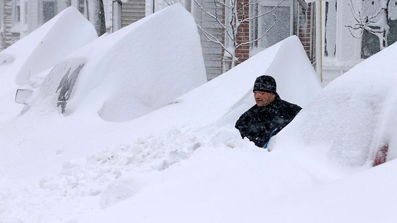 John Silver shovels snow between buried cars in front of his home on Third Street in South Boston, Saturday, Feb. 9, 2013. (AP / Gene J. Puskar)