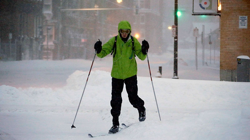 A pedestrian uses skis to travel through the deserted snow-covered streets of Boston early Saturday, Feb. 9, 2013. (AP / Gene J. Puskar)