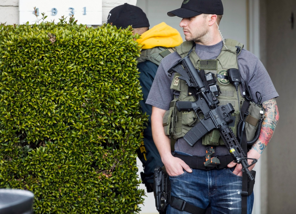 U.S. Marshals deputies look behind the vegetation as they stand on guard outside the home of the mother of fugitive suspect Christopher Dorner, a former Los Angeles officer in La Palma, Calif., on Friday, Feb. 8, 2013. ( AP / Damian Dovarganes)