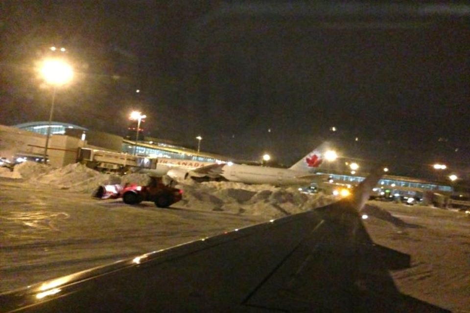 This photo submitted by a passanger on board a flight from Toronto to Saskatoon shows piles of snow on the Saskatoon tarmac.