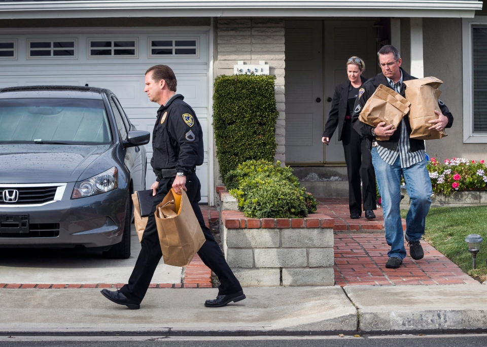 Police investigators take away evidence from the home of the mother of fugitive suspect former Los Angeles police officer Christopher Dorner, in La Palma, Calif., on Friday, Feb. 8, 2013. (AP / Damian Dovarganes)
