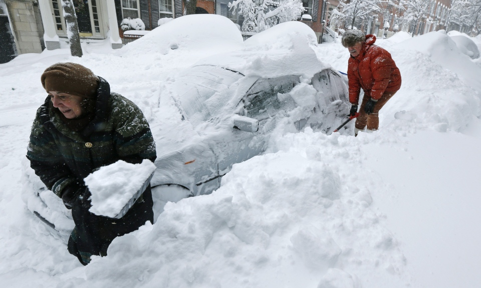 Deb Hanley, left, and Frank McGuire dig about three feet of snow from around their car outside their home in the Beacon Hill neighborhood of Boston on Saturday, Feb. 9, 2013.  (AP / Charles Krupa)