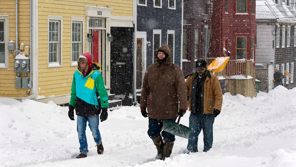 Three men head down a snowy street in Halifax as a major winter storms sweeps through Atlantic Canada on Saturday, Feb. 9, 2013. (Andrew Vaughan / THE CANADIAN PRESS)