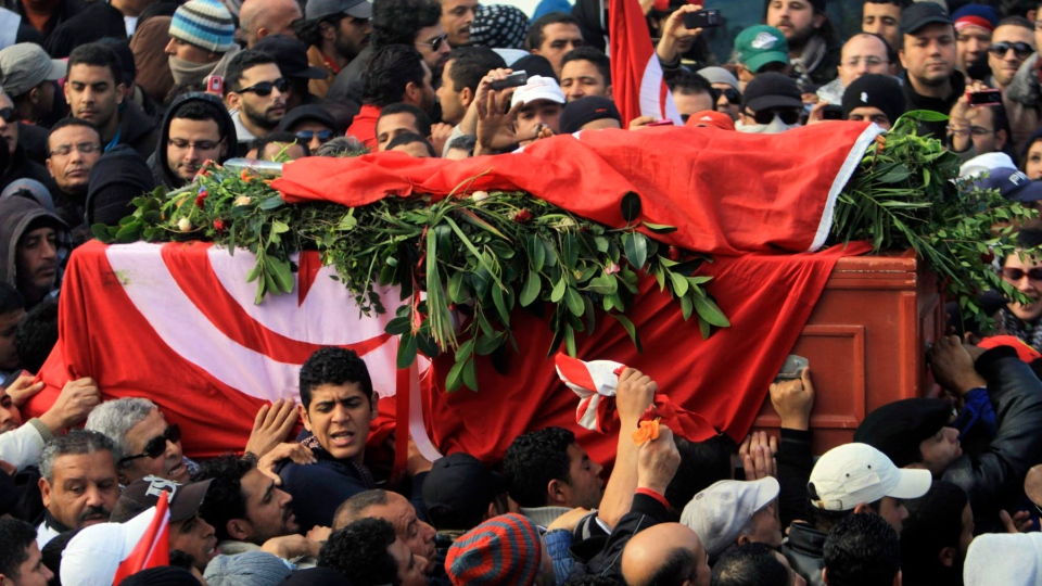 Pallbearers carry the coffin of Chokri Belaid as thousands of Tunisians are gathered at el Jallez cemetary to attend the funerals of the slain opposition leader, near Tunis, Friday, Feb. 8, 2013. (AP)