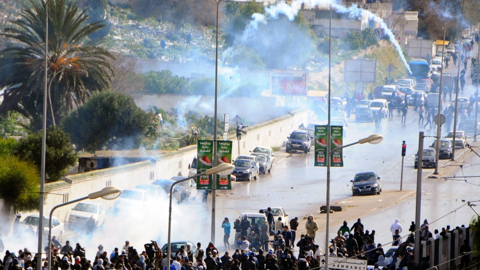 A tear gas canister flies in the air as thousands of Tunisians are gathered at el Jallez cemetery to attend the funerals of slain opposition leader Chokri Belaid, near Tunis, Friday Feb. 8, 2013. (AP / Hassene Dridi)