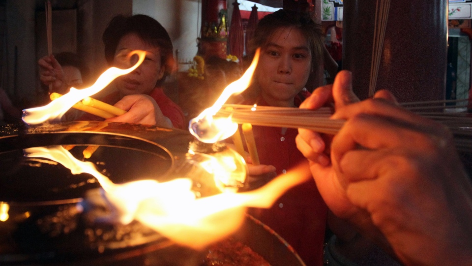 Ethnic Chinese peoples burn joss sticks to celebrate eve of Chinese Lunar New Year at Hea Tek Tunk Chinese Temple in Bangkok, Thailand, Saturday, Feb. 9, 2013. (AP Photo / Sakchai Lalit)
