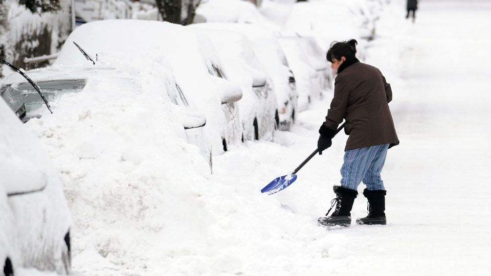 Tina Khoshaboo clears snow from her car on South Water Street during the aftermath of a blizzard in the Byram section of Greenwich, Conn., Saturday morning, Feb. 9, 2013. (AP Photo / Greenwich Time, Bob Luckey)