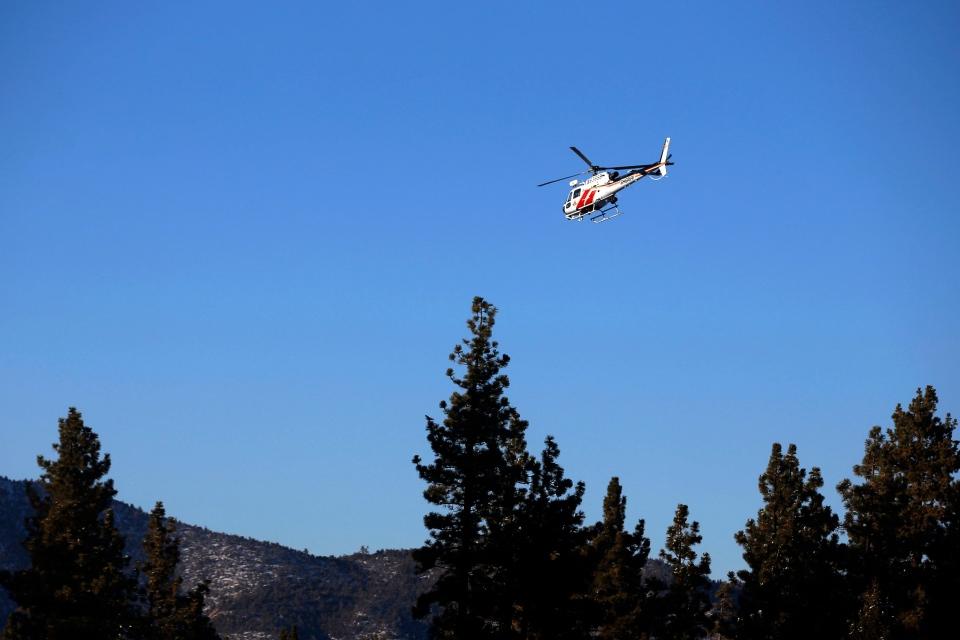 A San Bernardino County Sheriff's helicopter flies over Big Bear Lake, Calif., on Feb. 9, 2013. (AP / Jae C. Hong)