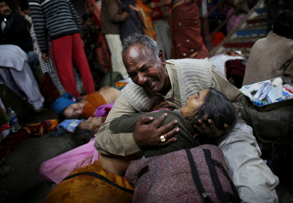 An Indian man weeps as he holds his wife who was killed in a stampede on a railway platform at the main railway station in Allahabad, India, on Feb. 10, 2013. (AP / Kevin Frayer)