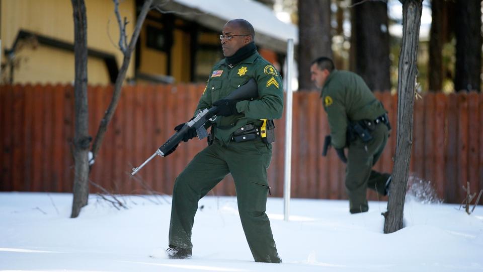 San Bernardino County Sheriff's officers Ken Owens and Bernabe Ortiz search a home for former Los Angeles police officer Christopher Dorner in Big Bear Lake, Calif, Sunday, Feb. 10, 2013. (AP / Jae C. Hong)