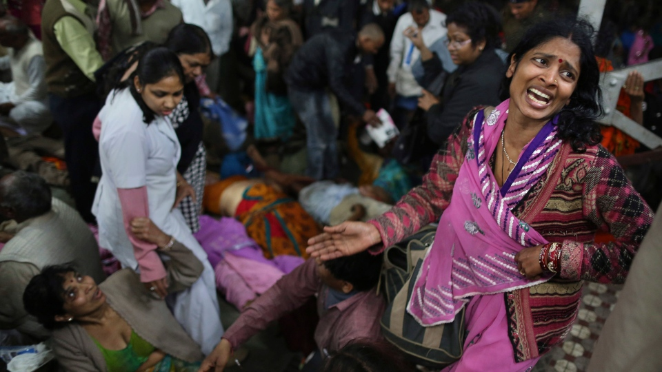 An Indian woman weeps as she and other family members mourn next to the body of a relative who was killed in a stampede on a railway platform at the main railway station in Allahabad, India, Sunday, Feb. 10, 2013. (AP / Kevin Frayer)
