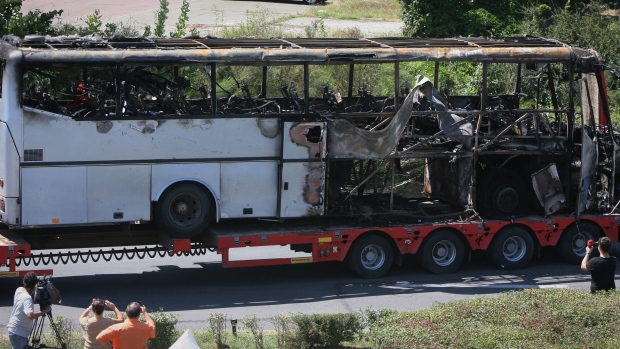 A damaged bus is transported out of the airport a day after a deadly suicide attack on a bus full of Israeli vacationers in Burgas, Bulgaria, Thursday, July 19, 2012. (Impact Press Group)
