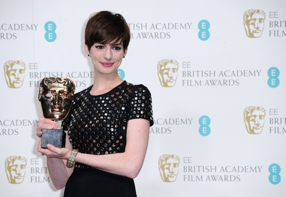 Actress Anne Hathaway poses backstage with the award for Supporting Actress for her role in 'Les Miserables,' at the BAFTA Film Awards at the Royal Opera House in London on Sunday, Feb. 10, 2013. (Invision / AP / Jonathan Short)