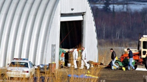 Investigators sort through evidence at the Roszko farm near Mayerthorpe, Alta., Saturday, March 5, 2005. (Jeff McIntosh / THE CANADIAN PRESS)