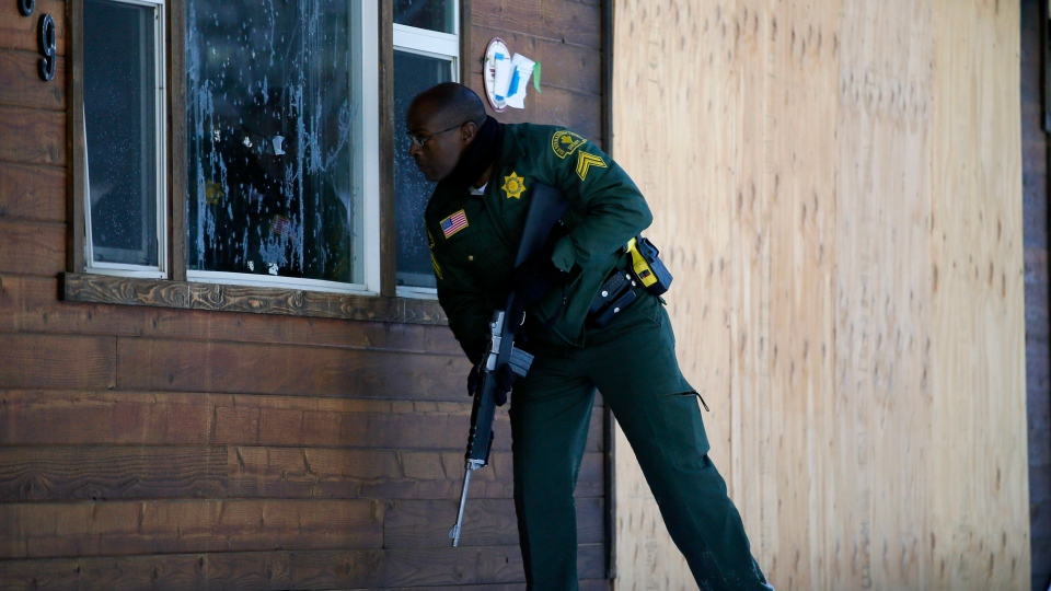 San Bernardino County Sheriff's officer Ken Owens searches a home for the former Los Angeles police officer Christopher Dorner in Big Bear Lake, Calif, Sunday, Feb. 10, 2013. (AP Photo / Jae C. Hong)