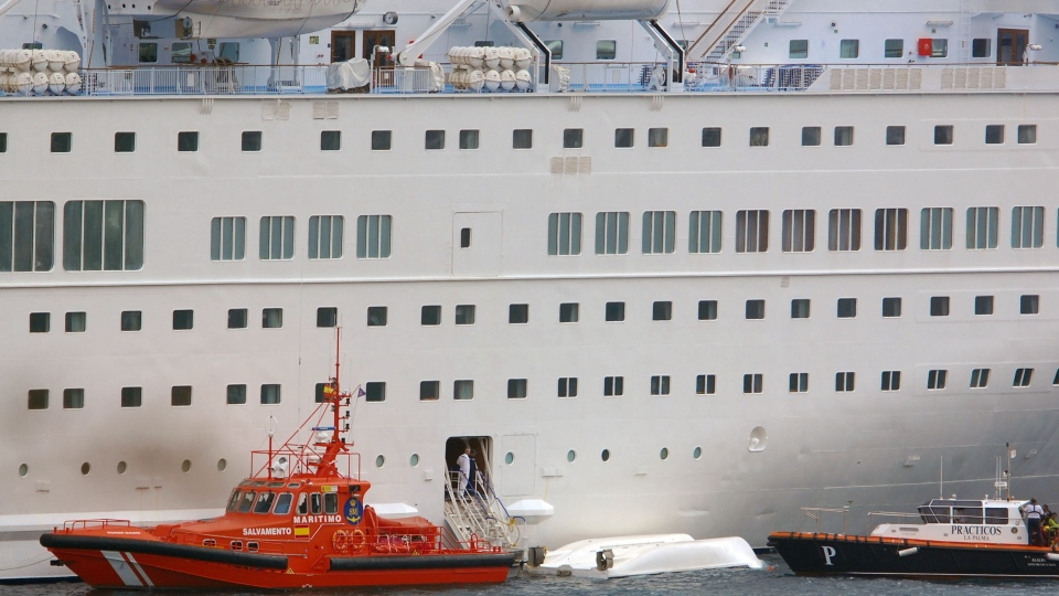 An orange rescue boat docks by a capsized lifeboat from the British-operated cruise ship Thomson Majesty in Santa Cruz port of the Canary Island of La Palma, Spain, Sunday Feb. 10, 2013. (AP Photo / Manuel Gonzalez)