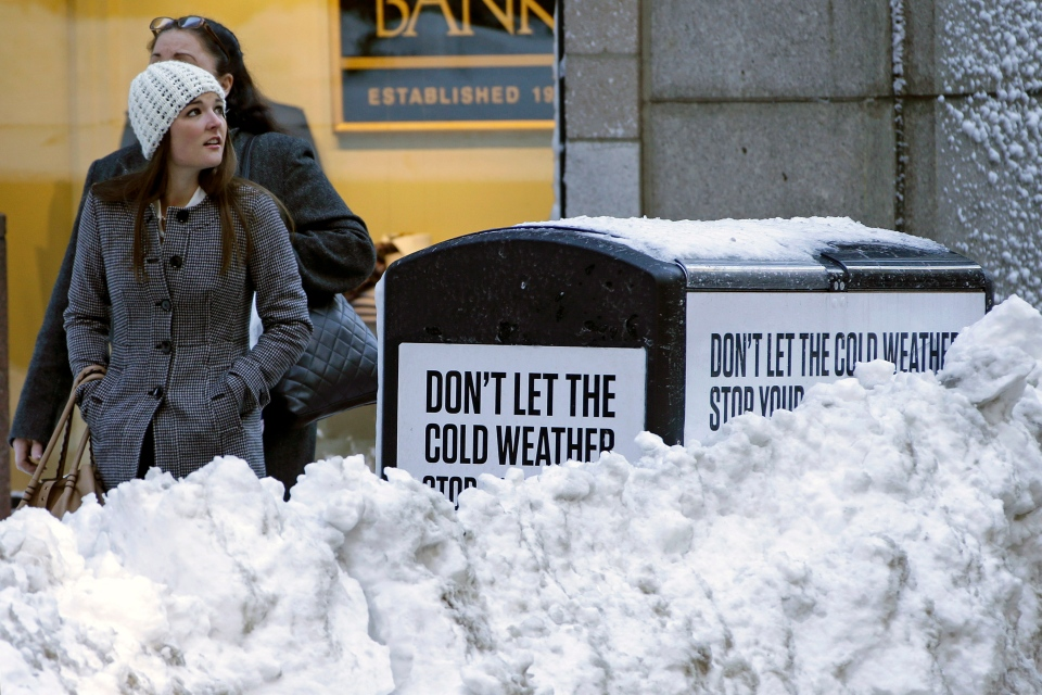A woman walks through downtown Boston on a sunny Sunday afternoon, Feb. 10, 2013. The city continues to dig out from the two-feet off snow that fell on Friday and Saturday. (AP Photo/Gene J. Puskar)
