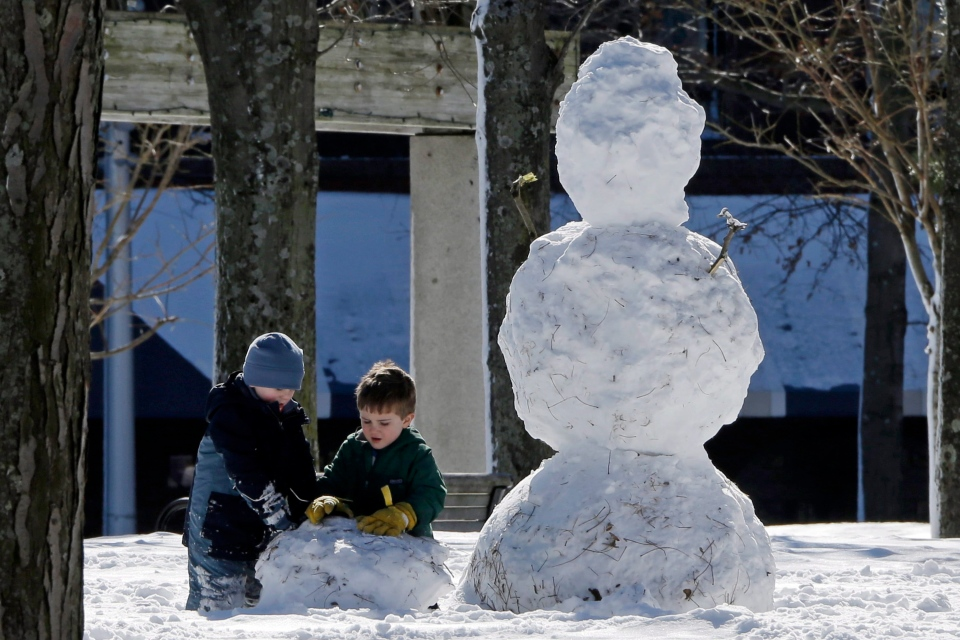 A couple of young boys play near a snowman in Christopher Columbus Park in the North End neighborhood of Boston on a sunny Sunday afternoon, Feb. 10, 2013. (AP / Gene J. Puskar)