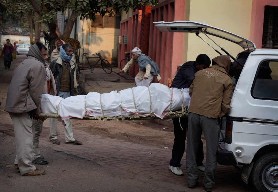 An Indian family puts the body of their relative who died in a stampede at a railway station into an ambulance for taking home from morgue, in Allahabad, India, Monday, Feb. 11, 2013. (AP / Rajesh Kumar Singh)
