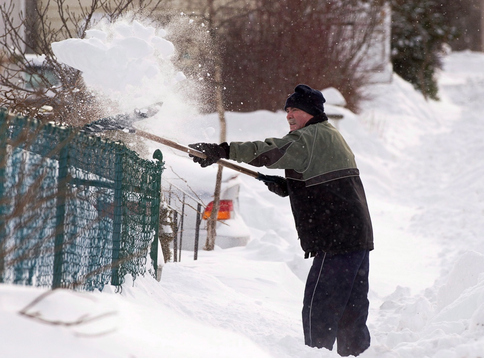 A resident clears his sidewalk in Dartmouth, N.S. on Sunday, Feb. 10, 2013. (Andrew Vaughan / THE CANADIAN PRESS)