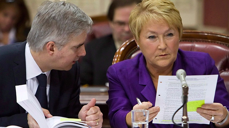Quebec Premier Pauline Marois listens to secretary-general of the executive council, Jean St-Gelais during a parliamentary commission about her expenses, in Quebec City, Thursday, Feb.7, 2013. (Clement Allard / THE CANADIAN PRESS)