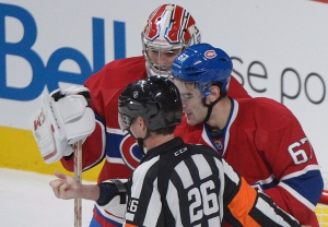 Montreal Canadiens' Max Pacioretty, right, shows his arm to a referee following an incident with Toronto Maple Leafs' Mikhail Grabovski as Canadiens' goaltender Carey Price looks on during third period NHL hockey action in Montreal on Feb. 9, 2013. (Graham Hughes/THE CANADIAN PRESS)