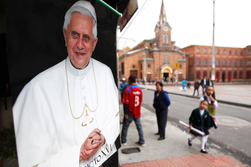 A poster of Pope Benedict XVI hangs on a store of religious paraphernalia next to the Baby Jesus Church in Bogota, Colombia, Monday, Feb. 11, 2013. (AP / Fernando Vergara)